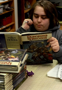 Devon McKinley pores over D&D manuals during a game session at the Wizard's Guild. Photo by Evan Chwalek.