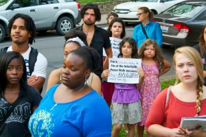 A family proudly holds up their signs at the Interfaith Peace Walk, to show why they participated. PHOTO CREDIT: Lauren Prescott