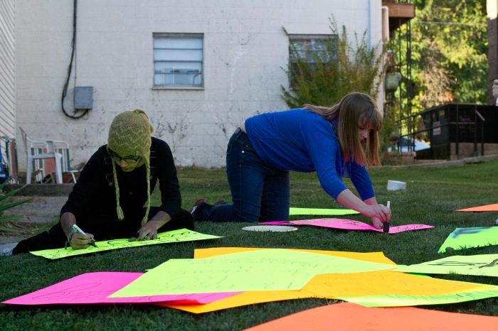 Sophomore Wren Jackson and co-president senior Allie Erwin work on their posters for Friday's rally at Mackracken Field.