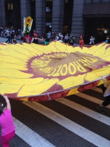 Activists bear the weight of a sunflower parachute as they walk the streets of New York. Photo by Evan Kreager.