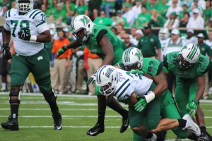 Ohio quarterback J.D. Sprague is sacked by Marshall defensive lineman Steve Dillion during the fourth quarter. (Photo by Zak Kolesar)