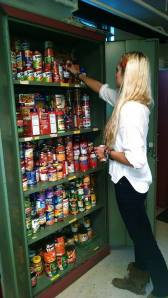 Senior, April Peterson stacks and organizes canned goods donated to United Campus Ministry. Photo courtesy of Sarah Franks.