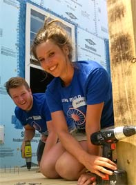 Emser and fellow rider work at a build site on their 2013 trip. Photo from 2013 newsletter.
