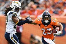 Devontae Booker (23) of the Denver Broncos stiff arms Dwight Lowery (20) of the San Diego Chargers during the second quarter on Sunday, October 30, 2016. The Denver Broncos hosted the San Diego Chargers. (Photo by John Leyba/The Denver Post)